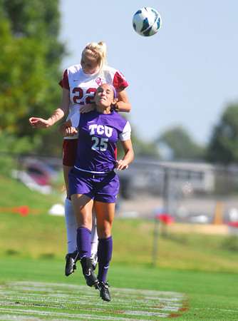 Oklahoma midfielder Alison Farrell (22) heads the ball to get it away from TCU's Becca Rowland (25) Sunday during the Sooners game at John Crain Field.<br /> Kyle Phillips/The Transcript