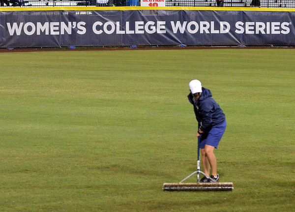 A grounds crew member squeegees water off the outfield after a rain delay, Wednesday, June 6, 2012, prior to the third game of the Womens College World Series championship at ASA Hall of Fame Stadium in Oklahoma City. Jerry Laizure / The Transcript