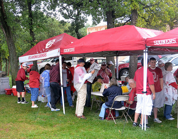 Members of the OU Diamond Club, the booster club for Sooner softball, took refuge under their tents, Wednesday, June 6, 2012, during the rain delay the third game of the Womens College World Series championship at ASA Hall of Fame Stadium in Oklahoma City. Jerry Laizure / The Transcript