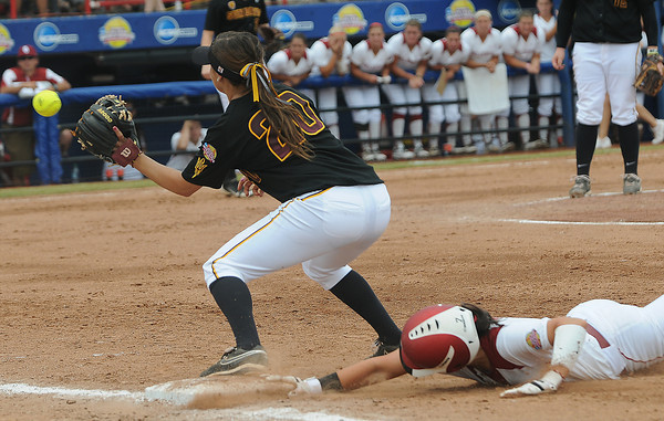 Oklahoma's Javen Henson dives back to base while Arizona State first baseman Annie Lockwood (20) waits on the throw, Sunday, June 3, 2012, in a semifinal game of the Womens College World Series at ASA Hall of Fame Stadium in Oklahoma City. Jerry Laizure/The Transcript