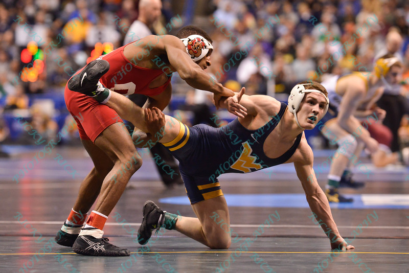 ZEKE MOISEY of West Virginia looks to his coaches for advise against NAHSHON GARRETT of Cornell during the second round of the championship bracket of the NCAA division 1 wrestling championships held at Scottrade Center in St. Louis MO.