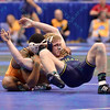 GEORGE FISHER of Michigan is tied up from behind by JORDAN LASTER of Princeton during the second round of the wrestleback bracket of the NCAA division 1 wrestling championships held at Scottrade Center in St. Louis MO.