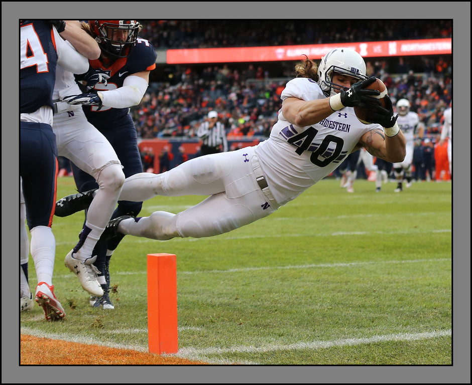 Northwestern University's Dan Vitale (40) takes a screen pass, follows a block, and dives into the endzone for a first half touchdown against the Illini, November 28, 2015, Chicago, Illinois.  Photo credit: Allen Cunningham
