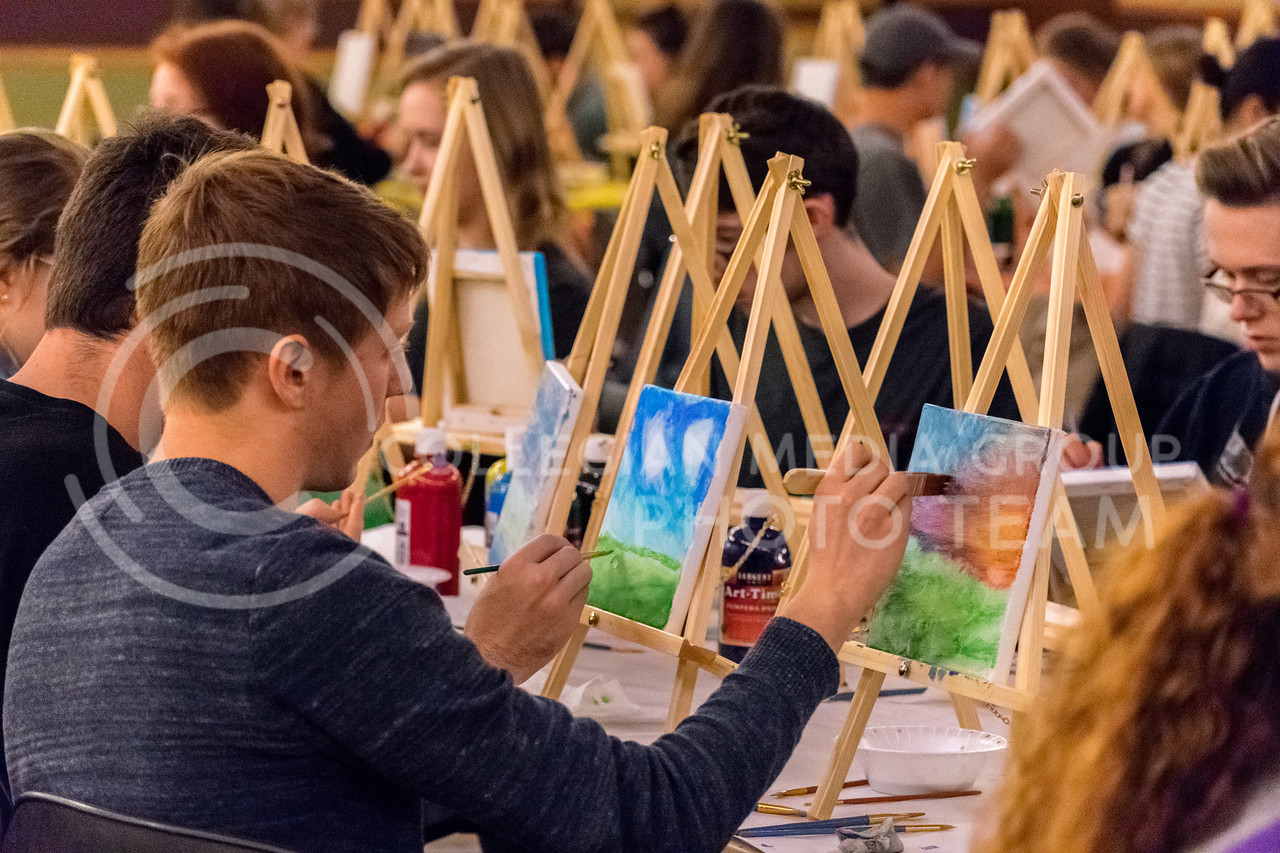 A student creates a vivid Kansas sunset at the Happy Trees Painting event on January 26. (Alex Todd | Collegian Media Group)