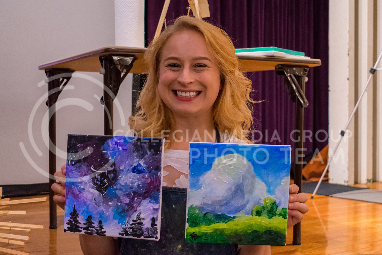 Jessie Burnes, Senior in Fine Arts, poses with her two paintings. She lead over 400 students on a creative adventure on Friday night in the Union Ballroom. (Alex Todd | Collegian Media Group)