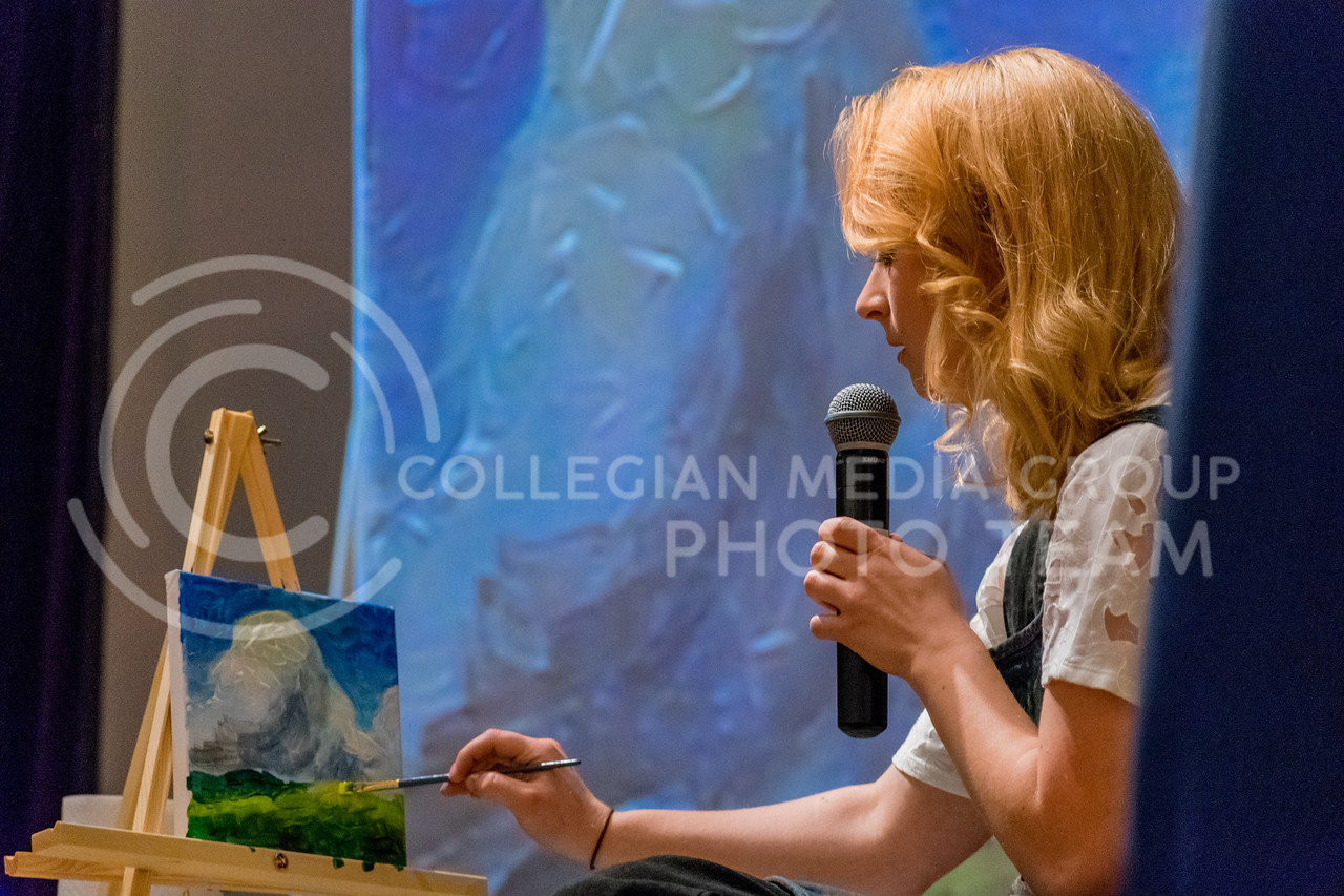 Jessie Burnes goes over how to add different colored layers of grass to add depth to a painting. (Alex Todd | Collegian Media Group)