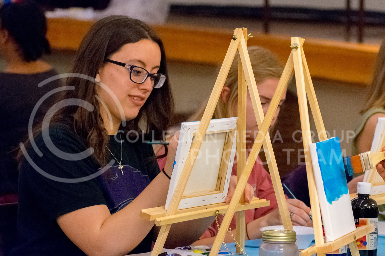 Sophomore in Nutrition and Health Isabelle Cyrier starts to add a bright blue to create her sky scenery at the Happy Trees Painting event on January 26. (Alex Todd | Collegian Media Group)