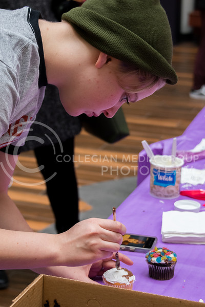 Abi Compton, sophomore in fine arts, delicately brushes chocolate icing on her cupcake at the UPC Battle of the Cupcakes in the Union on February 21. (Alex Todd | Collegian Media Group)