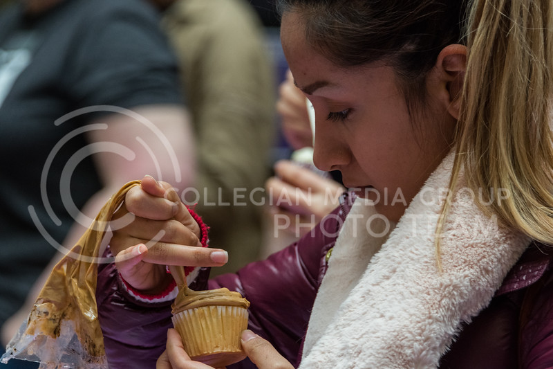 K-State student Zhila Pezeshkpoor squeezes icing onto the top of her cupcake at the UPC Battle of the Cupcakes that took place in the Union on February 21. (Alex Todd | Collegian Media Group)