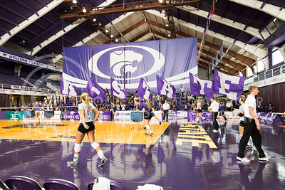 The K-State cheerleaders run with the flags across Ahearn Field House before the K-State versus Mississippi State volleyball game on Sept. 9, 2016. (Anna Spexarth | The Collegian)