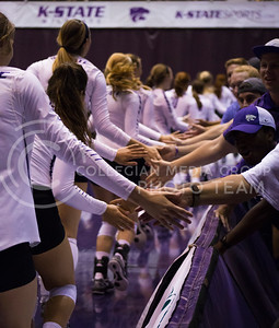 Students high-five volleyball players, celebrating K-State's win over Miami in Ahearn Field House on Sept. 9, 2016. (Anna Spexarth | The Collegian)