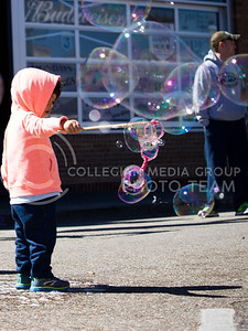 Rodean Tonek, 2, holds a bubble wand and lets the wind blow bubbles during the Mini Maker Faire held in Aggieville on Sept. 10, 2016. (Alanud Alanazi | The Collegian)