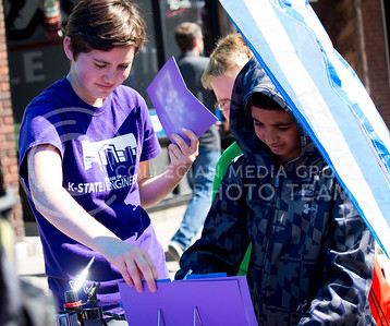 A K-State College of Engineering representative helps a fair attendee during the Mini Maker Faire held in Aggieville on Sept. 10, 2016. (Alanud Alanazi | The Collegian)