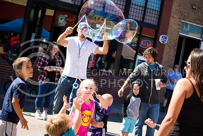 Fair attendees prepare to jump to pop a bubble during the Mini Maker Faire held in Aggieville on Sept. 10, 2016. (Alanud Alanazi | The Collegian)