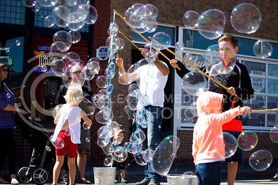 Fair attendees blow and pop bubbles during the Mini Maker Faire held in Aggieville on Sept. 10, 2016. (Alanud Alanazi | The Collegian)