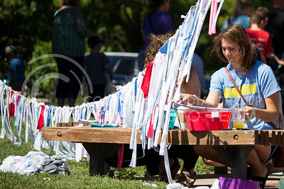 A Faire attendee hangs a piece of cloth with her writing on a rope during the Mini Maker Faire held in Aggieville on Sept. 10, 2016. (Alanud Alanazi | The Collegian)