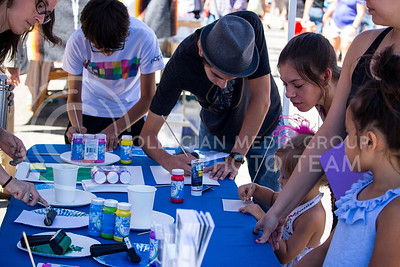 Fair attendees paint paper plates during the Mini Maker Faire held in Aggieville on Sept. 10, 2016. (Alanud Alanazi | The Collegian)
