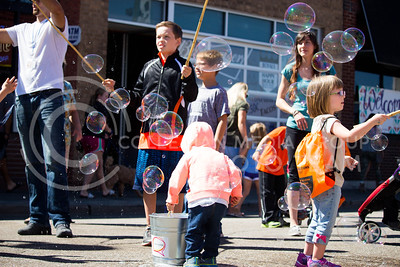 Fair attendees burst and blow bubbles provided by the Indescribubble booth during the Mini Maker Faire held in Aggieville on Sept. 10, 2016. (Alanud Alanazi | The Collegian)