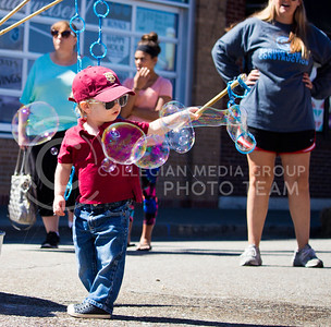 Vance Shwartz, 2, holds a wand out as the wind blows bubbles during the Mini Maker Faire held in Aggieville on Sept. 10, 2016. (Alanud Alanazi | The Collegian)