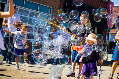 Fair attendees jump and blow bubbles, provided by the Indescribubble booth during the Mini Maker Faire held in Aggieville on Sept. 10, 2016. The fair is hosted to celebrate local maker culture and encourage conversation with local makers. (Alanud Alanazi | The Collegian)