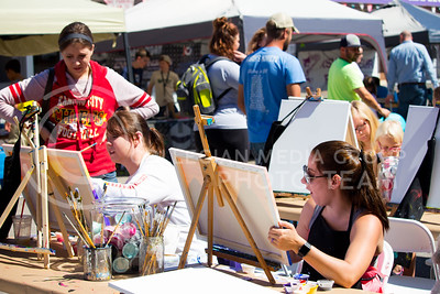 Fair attendees paint the Kansas sunset at a painter's booth during the Mini Maker Faire held in Aggieville on Sept. 10, 2016.  (Alanud Alanazi | The Collegian)