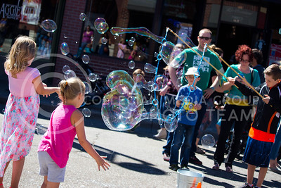 Fair attendees wait for the bubbles to hit them, provided by the Indescribubble booth during the Mini Maker Faire held in Aggieville on Sept. 10, 2016. (Alanud Alanazi | The Collegian)