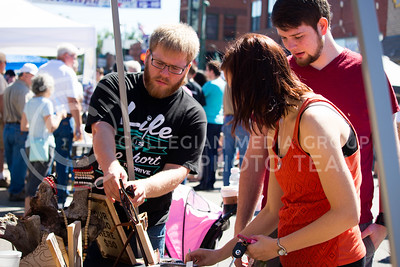 A Horizon Design and Woodworking representative helps fair attendees during the Mini Maker Faire held in Aggieville on Sept. 10, 2016. (Alanud Alanazi | The Collegian)