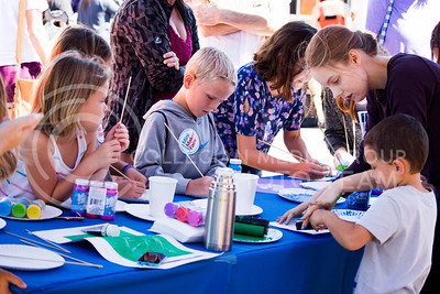 Fair attendees paint paper plates during the Mini Maker Faire held in Aggieville on Sept. 10, 2016. The fair is hosted to celebrate local maker culture and to allow the community to converse with local makers. (Alanud Alanazi | The Collegian)