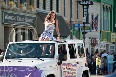 Miss Pottawatomie, Sheyenne Denton, sits atop a Jeep while waving to patrons in downtown during the annual parade on July 4, 2016. (Evert Nelson | The Collegian)