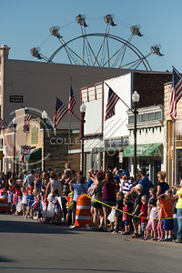 A ferris wheel peaks above buildings in downtown Wamego during the annual parade on July 4, 2016. (Evert Nelson | The Collegian)