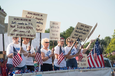 Women wave signs about what 'dems believe in' on a Pottawatomie County Dems float during the annual parade on July 4, 2016. (Evert Nelson | The Collegian)
