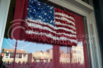 A colorful American Flag hangs in the shop window off Downtown Wamego while the annual parade reflects on July 4, 2016. (Evert Nelson | The Collegian)