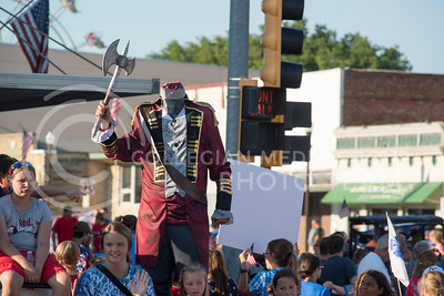 A person in a headless-horsman outfit waves an ax on a parade float to promote local performing arts during the annaula parade through downtown on July 4, 2016. (Evert Nelson | The Collegian)