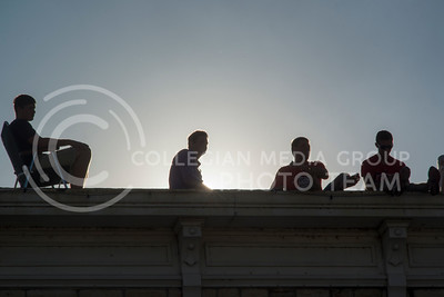 Guys hang out on the top of a building overlooking downtown Wamego during the annual parade on July 4, 2016. (Evert Nelson | The Collegian)