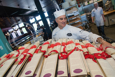Wade Radina, co-owner of the coffeeshop and bakery chain in Manhattan, picks up a couple of the 400 bagettes that he prepared that morning to give to patrons of the Taste of Downtown on June 7, 2016. (Photo by Evert Nelson | The Collegian)
