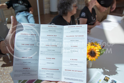 A volunteer of the Taste of Downtown shows the menu/ticket that patrons received as they made their way through 14 businesses sampling what they had to offer. (Photo by Evert Nelson | The Collegian)