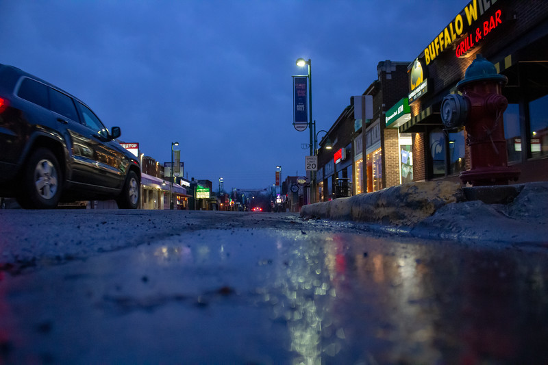 Aggieville sines with rain in the morning. Little people in the streets as the lights glow. (Abigail Compton)