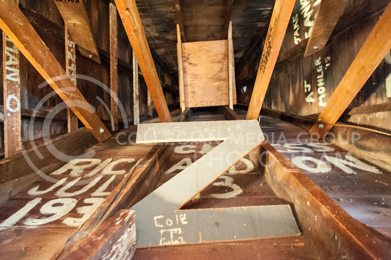 A collection of names painted in white, engraved into the wood and even custom pieces of wood add character to the bell tower inside Anderson Hall on October 10, 2016. Some names date back to the 1920s and 30's while some show more recent dates. (Evert Nelson | The Collegian)