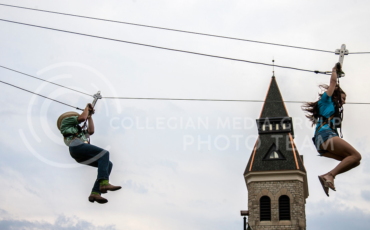 Flying high above Anderson Hall lawn, Trenton Heinen, sophomore in english (left), rides down a zipline with Becca Fugara, 5th year in csd. The zipline was one of the activies at this years UPC Expo Thursday afternoon.