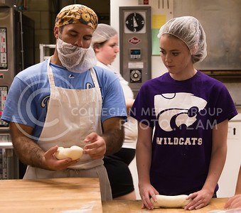 Gideon Abel Butler Smith, senior in bakery science, demonstrates to Janae Brown, freshman in bakery science, how to form a vienna roll during a Bakery Science Club meeting in Shellenberger Hall on Sept. 20, 2016. The goods baked at the meeting that night were sold at the Bakery Science Club's bake sale the next day. (Anna Spexarth | The Collegian)