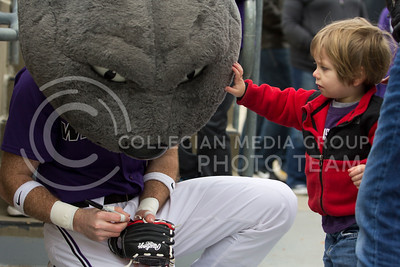 A child at the baseball game pats Willie on the head while he gets his glove signed during the K-State game against TCU at Tointon Stadium on Apr. 1 2017. (Sabrina Cline | The Collegian)