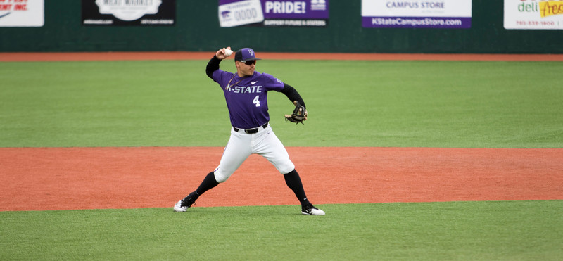 Freshman infielder Dylan Watts fields and throws the ball from third base to first base for the out during the game against Oklahoma State at Tointon Family Stadium on Apr. 9 2018. ( Sabrina Cline | Collegian Media Group )