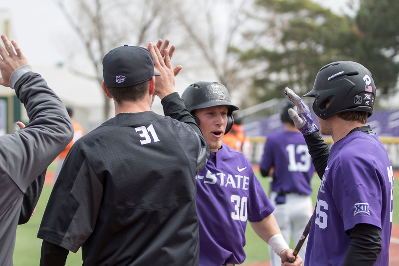 Junior infielder Drew Mount receives high fives from his teammates after scoring during the game against Oklahoma State at Tointon Family Stadium on Apr. 9 2018. ( Sabrina Cline | Collegian Media Group )