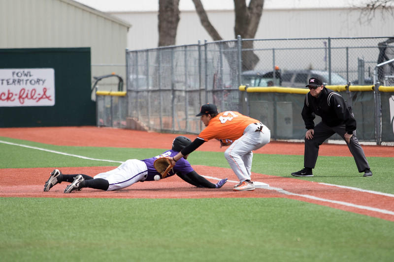Senior infielder Trent McMaster dives back to first base during the game against Oklahoma State at Tointon Family Stadium on Apr. 9 2018. ( Sabrina Cline | Collegian Media Group )