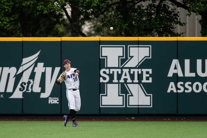 Kansas State University junior out fielder Will Brennan throws the ball back into the infield after catching a pop fly slapped by a Wichita State University player. The K-State Wildcats faced off against the Wichita State Shockers winning the single game series 7-2. (Olivia Bergmeier | Collegian Media Group)