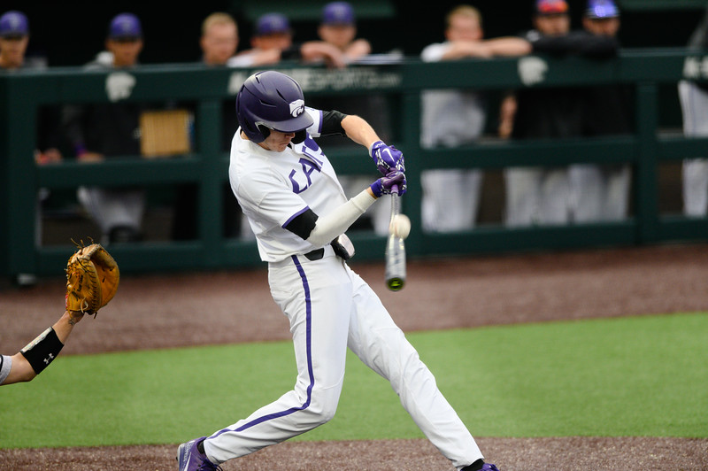 K-State junior right-handed pitcher Caleb Littlejim smacks a line drive to then make it on base for the Wildcats. The K-State Wildcats faced off against the Wichita State Shockers winning the single game series 7-2. (Olivia Bergmeier | Collegian Media Group)