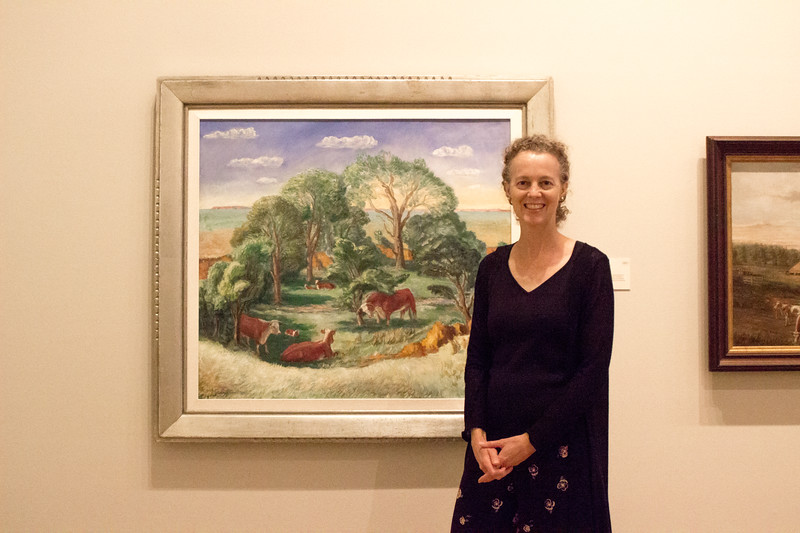 Elizabeth Seaton, one of the curators at the Marianna Kistler Beach Museum of Art, poses beside one of her favorite pieces in the gallery, Kansas Pasture a painting by John Steuart Curry, on Sept. 11th, 2019. (Sarah Millard | Collegian Media Group)