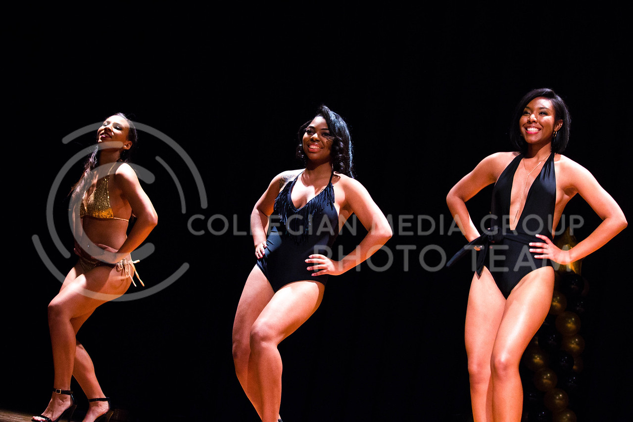 Melissa Riley, junior in Animal Science and Industry, Keneysha Mckinney, freshman in Business Adminstration, and Jaliyiah Brown, senior in Apparel and Textiles, model their swimsuits during the swimwear contest at the 18th Annual Black and Gold Pagent at the student union on Dec. 3.<br /> ( Alanud Alanazi | The Collegian)