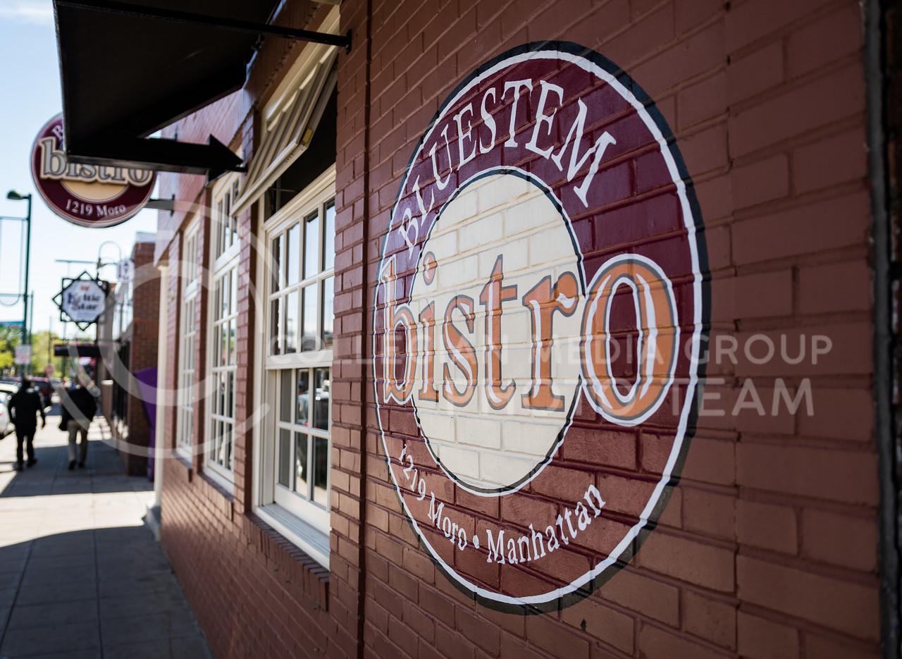 A Bluestem Bistro logo is displayed on the brick wall outside Bluestem Bistro on Apr. 27, 2017. (John Benfer | The Collegian)
