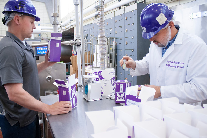 Jake Eckert (left), agricultural technician senior, fills a one container with purple pride ice cream while Jared Parsons, dairy plant manager, stamps freshly filled containers at Call Hall's dairy plant on Tuesday, April 24, 2018. (Tiffany Roney | Collegian Media Group)
